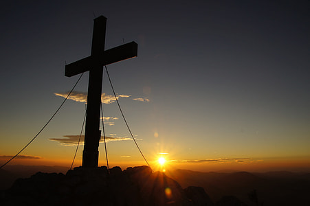 silhouette of cross decor during sunset
