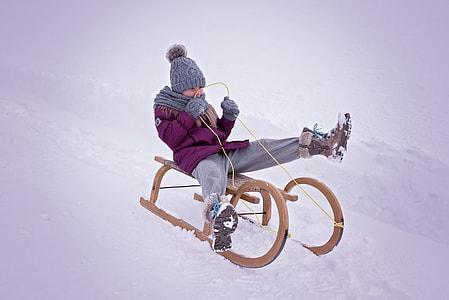 child riding sled