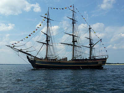 brown and green galleon ship on body of water during daytime