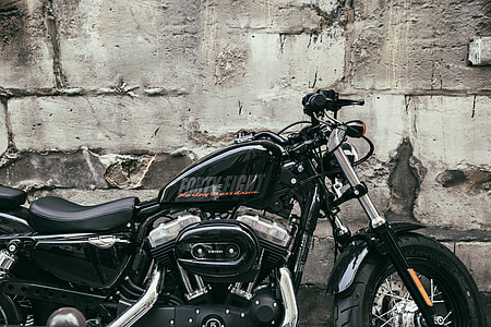 A Harley Davidson motorbike sits by a old wall in Paris, France. Image captured with a Canon 6D