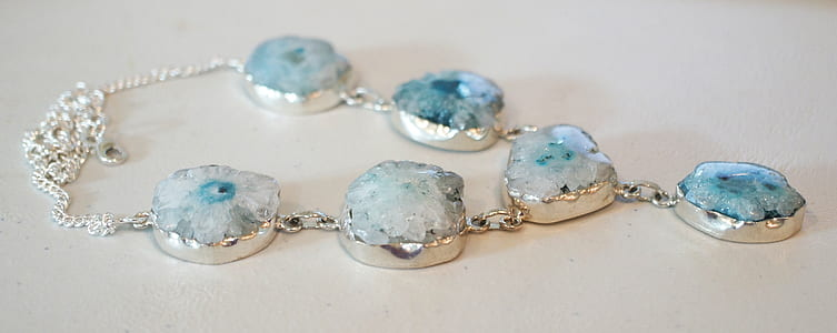 silver-colored teal stone necklace on white board