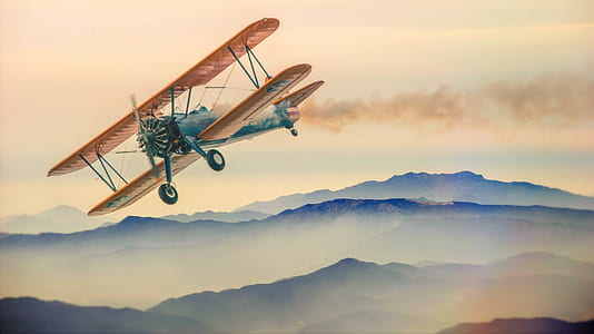 illustration of brown and blue biplane flying over mountain