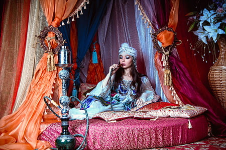 woman wearing blue long-sleeved dress and pagri hat sitting on bed smoking hookah