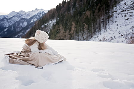 girl in brown dress on snowy mountain during daytime