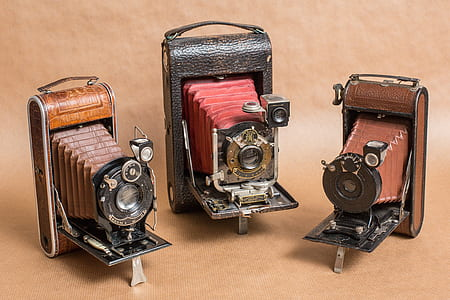 three vintage brown cameras