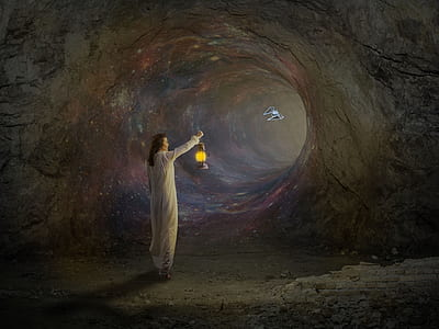 person holding lamp inside cave