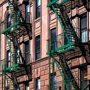green metal fire exit ladder on beige concrete building