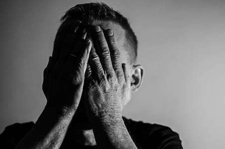grayscale photo of a man covering his face with both hands