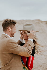 photo of man putting hat on woman