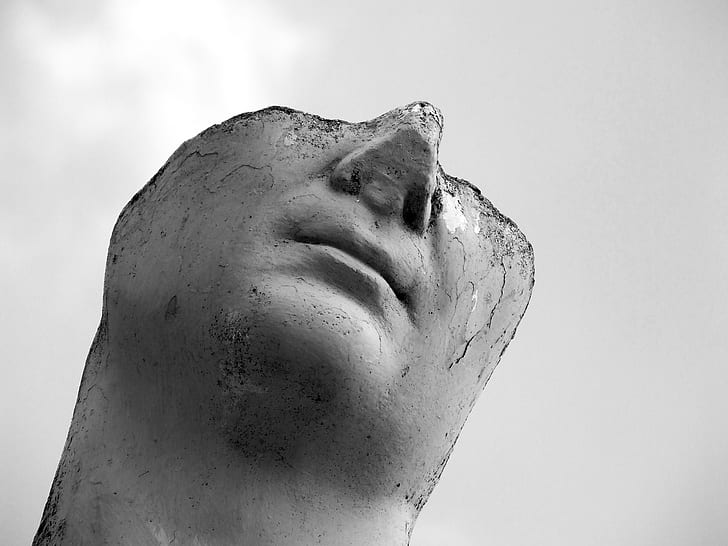 grayscale photo of beheaded statue