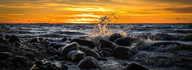 waves splashing through rocks during golden hour