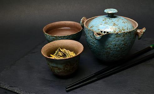 three blue-and-brown ceramic jars