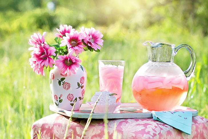 clear glass of pitcher with juice near glass full of juice and pink flowers in vase on table
