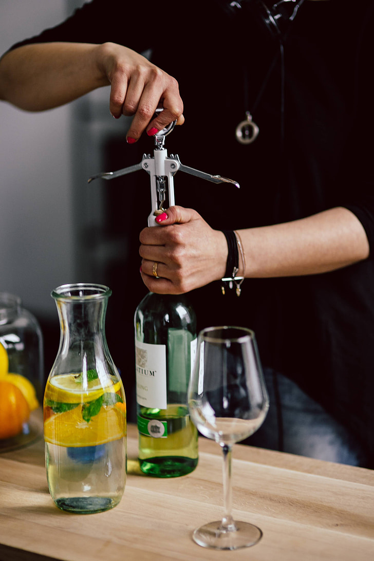 Hands opening wine bottle with corkscrew