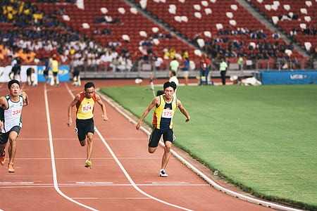 man in yellow tank top and black shorts running on track field