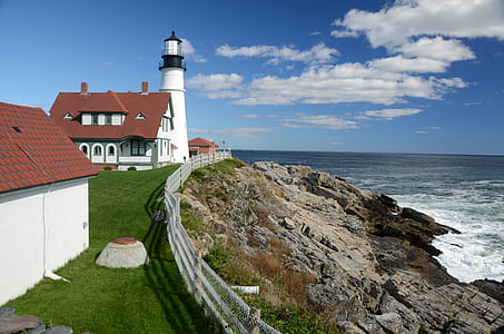 photography of lighthouse near sea during daytime