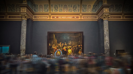 time lapse photo of people looking at painting on the wall