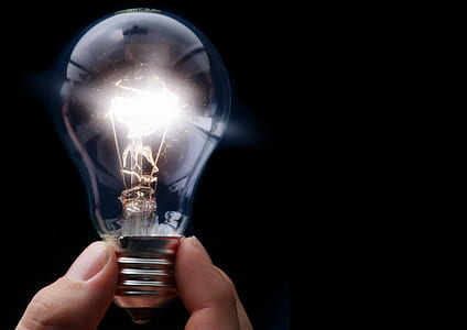 person holding lighted bulb