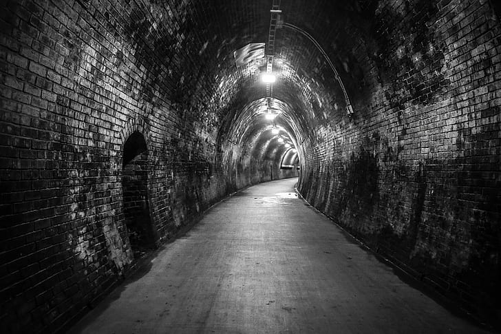 grayscale photo of tunnel with lights