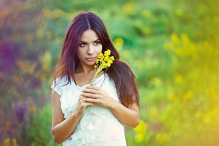 woman wearing black top holding yellow flowers