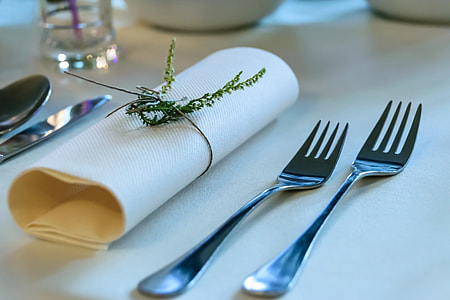two gray stainless steel forks beside white table napkin