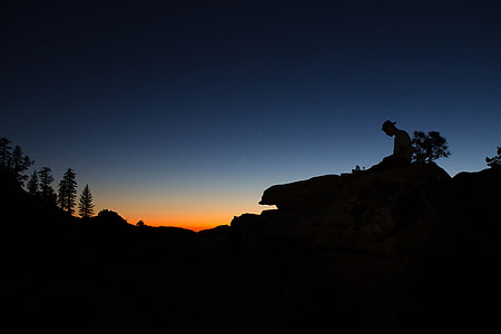 Silhouette of a man sitting on a rock at sunset in Yosemite Valley, USA
