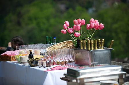 pink tulip flower arrangement beside wine glass and bottle on table
