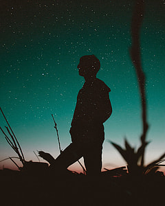 sillhouette of man staring at the sky during night