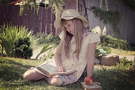 girl in yellow dress reading book sitting on green grass