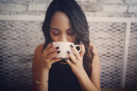 woman wearing black sleeveless top holding white ceramic teacup