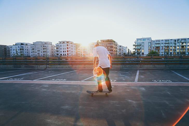 man wearing white t-shirt and black pants standing on skateboard during daytime