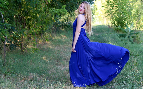 woman wearing blue halterneck sleeveless maxi dress outdoors