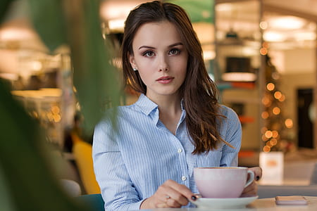 woman in blue shirt holding cup