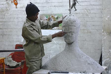 man sculpting head statue