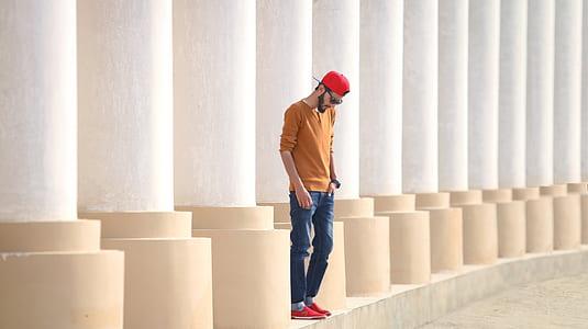 man standing between white pillars