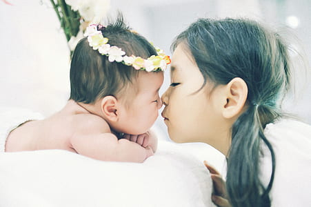 photo of girl kissing a baby