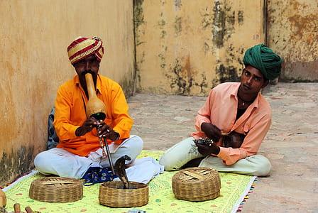 two men sitting on ground near brown baskets