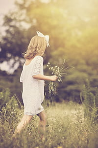 girl wearing white dress holding white flower bouquet while walking on grass field