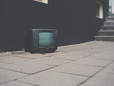 black CRT TV on brown brick