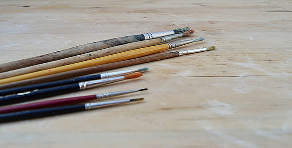 assorted-color paint brushes on brown table