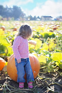 girl sitting on pumpkin