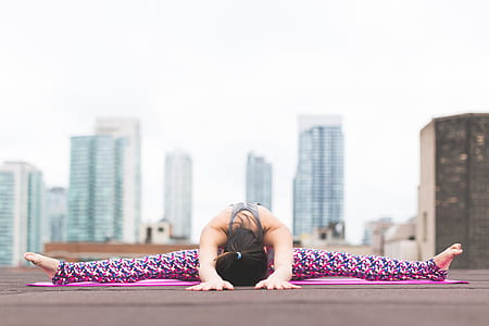 woman doing yoga with buildings on the background
