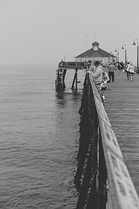 people on wooden dock grayscale photo