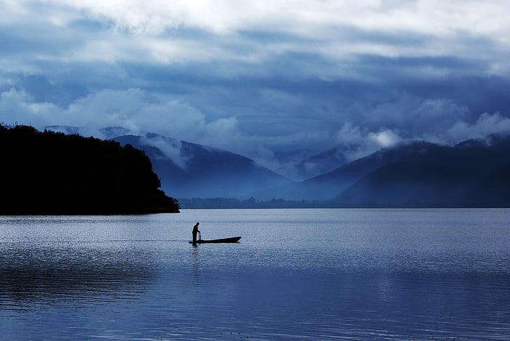 man in boat between ocean during twilight