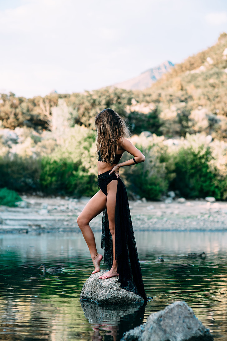 e32f3f4472a woman wearing black crop top standing at gray stone on body of water during  daytime