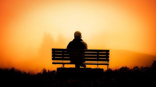 man sitting on a bench taken on sunset