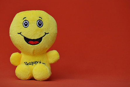 Happy Emoji plush toy with red-orange background