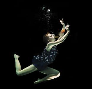 woman drinking wine under water