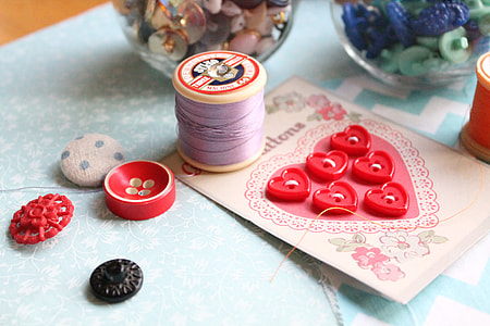photo of purple sewing thread beside red cloth button