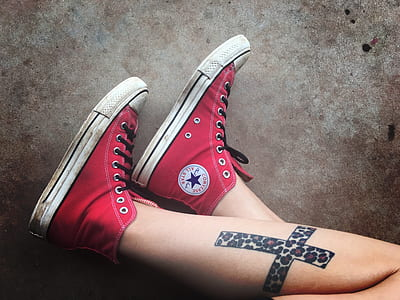 photo of person wearing red Converse Chuck Taylor high-rise